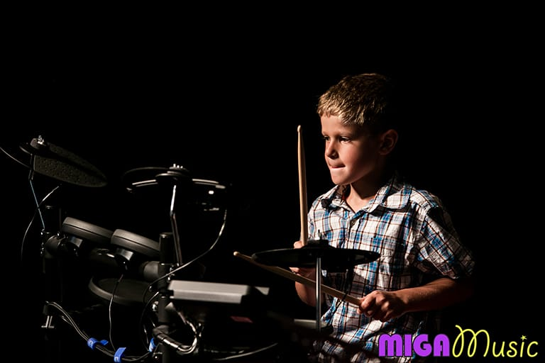MIGA Music student Joshua playing drums at our Recitals