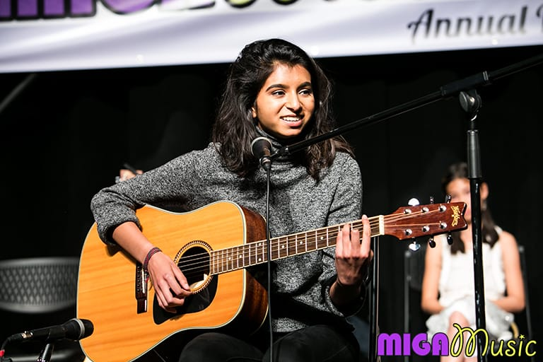 MIGA Music student Amal playing guitar at our Recitals