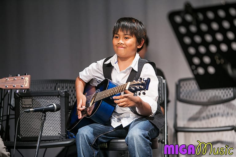 MIGA Music student Elai playing guitar at our Recitals