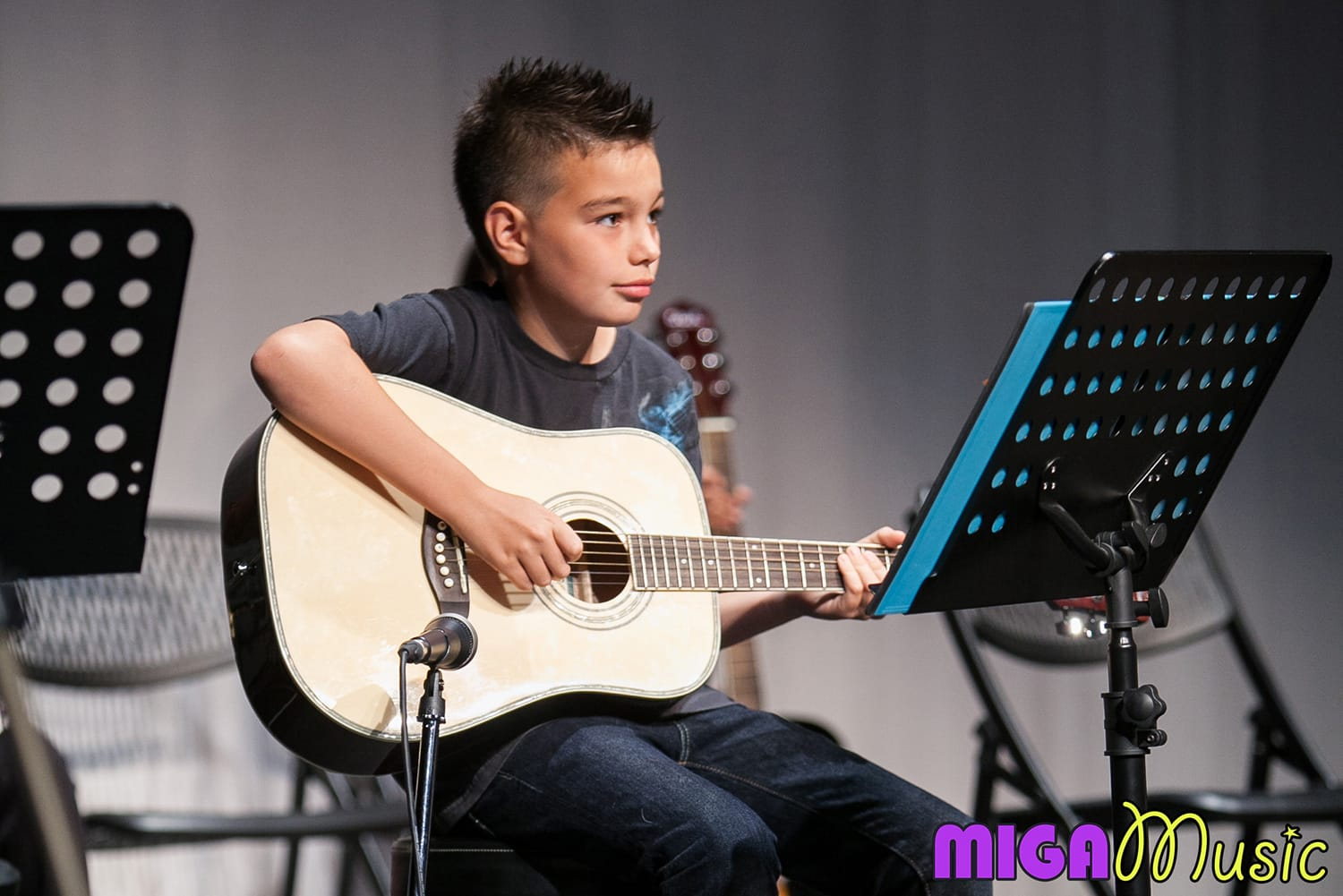 MIGA Music student Sebastian playing guitar at our Recitals