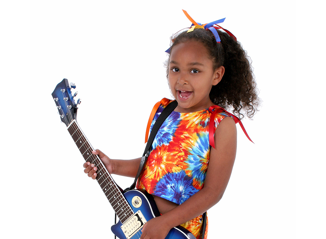 Guitar playing girl with a cute smile dressed in a colourful dress