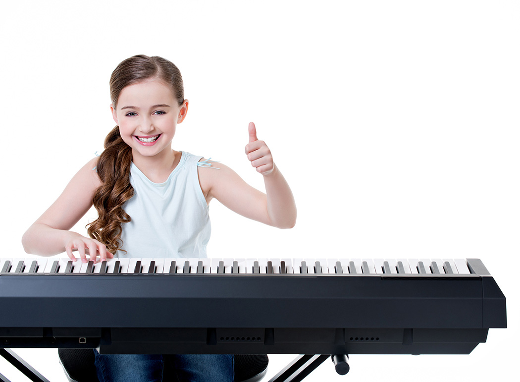 Girl playing piano and showing thumbs up