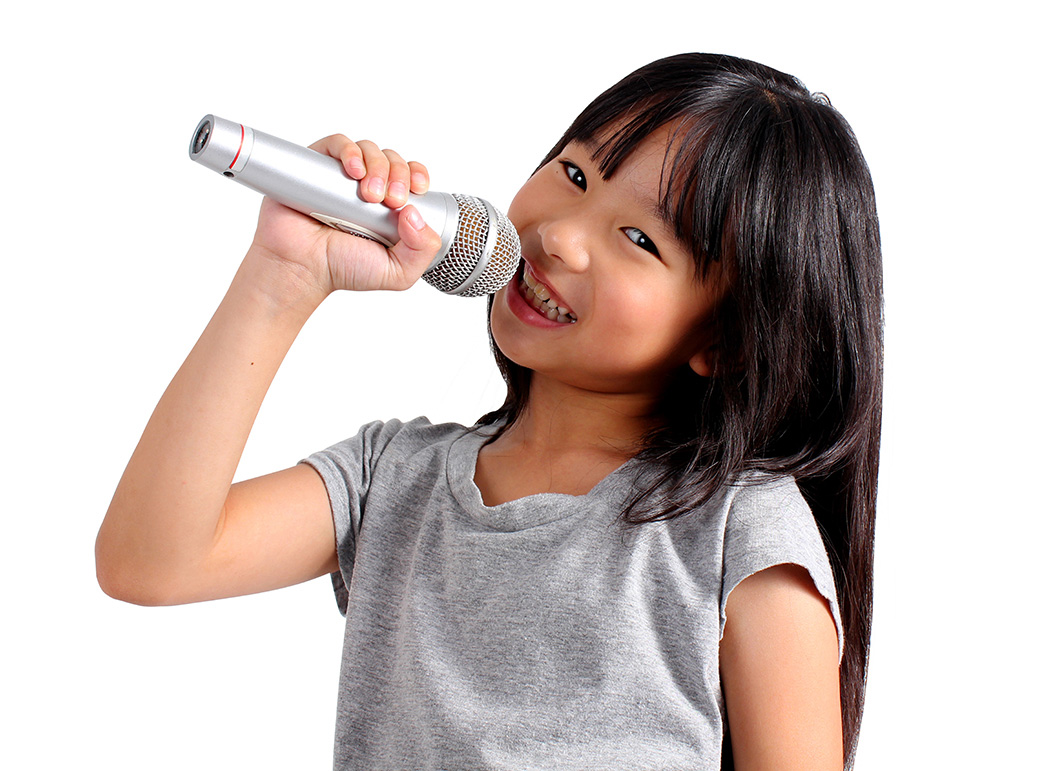 Girl singing holding a microphone and clearly enjoying it
