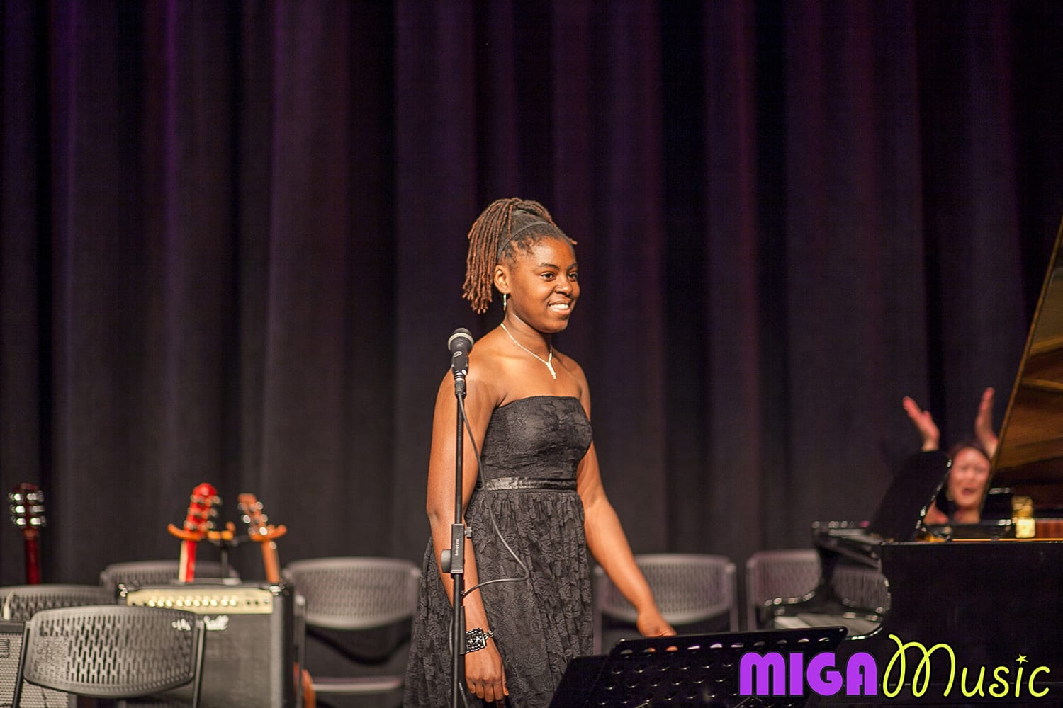 MIGA Music vocal student Samantha at our Recitals smiling and wearing a long black dress
